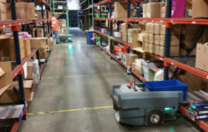 Autonomous mobile robot picking order from warehouse shelf.